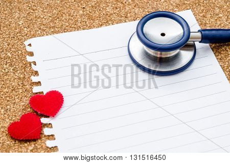 Blank paper note with stethoscope with red heart ready for your text or message on wood background.
