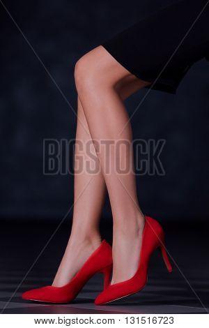 Female legs in elegant heeled shoes on dark background