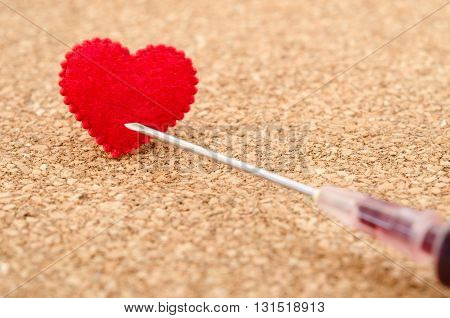 Red heart and needle syringe on wooden background. Heart Desease concept.
