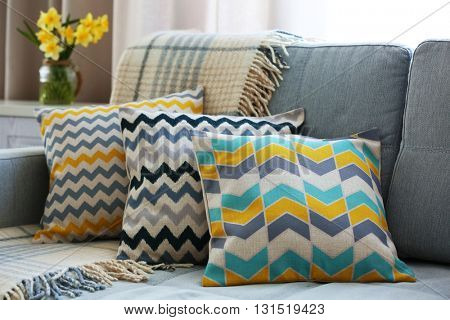 Stylish pillows on grey couch