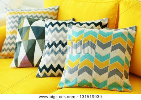 Stylish pillows on yellow couch