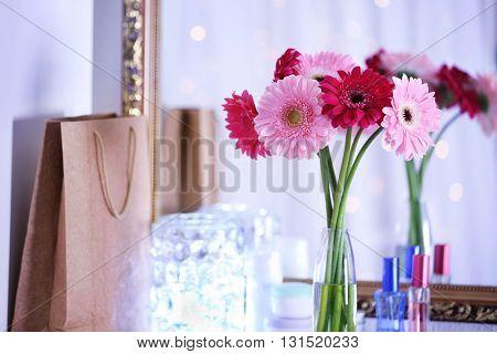 Bouquet of fresh gerbers in vase in front of the mirror indoors