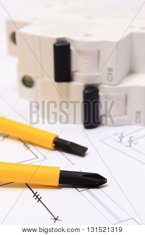 Screwdriver work tools and electric fuse lying on construction drawing of house accessories for engineering work
