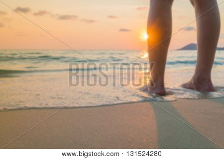 Blurred feet on the sand in sunset time