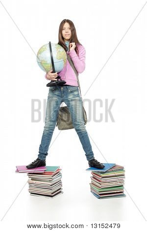 Portrait of a scoolgirl standing on a stack of books with her globe.