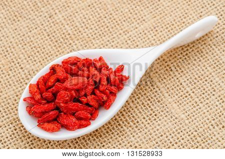 dry red goji berries for a healthy diet in white spoon on sack background.