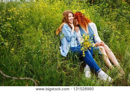 Best friends forever. Girlfriends gossiping in the park. BFF. A girl holding a bouquet of wildflowers. Embrace