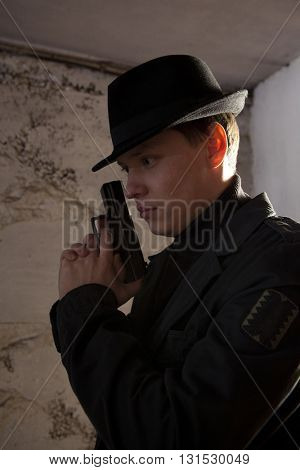 Man holding gun against an wall background