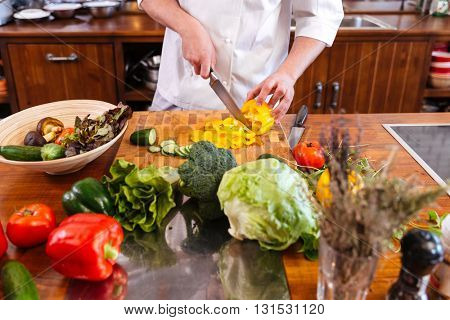 Closeup of chef cook standing and making salad on the kitchen