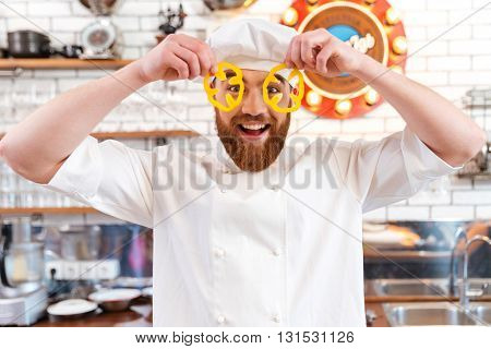 Happy funny chef cook looking through slices of yellow bell pepper on the kitchen