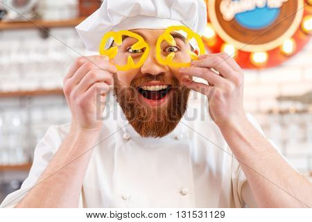 Cheerful amusing holding slices of yellow bell pepper in front of his eyes