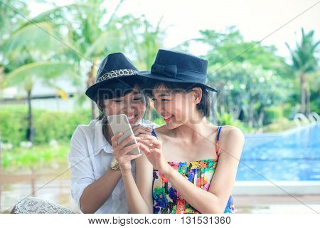 portrait of young beautiful asian woman laughing with happiness face looking to smart phone use for people and digital modern life connecting on line by mobile phone chat