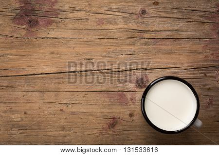 Brown weathered wooden board with white tin cup with milk as image background with copy-space.