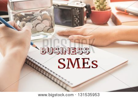 Businessman write SME word on book (small business concept)