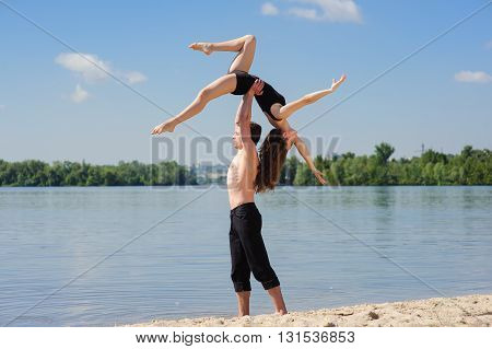 Man and woman in passionate dance pose on beach. Young couple dancing modern dance outdoors. Man with naked torso on sand. Man lifting woman above head. Sky and water river in background.