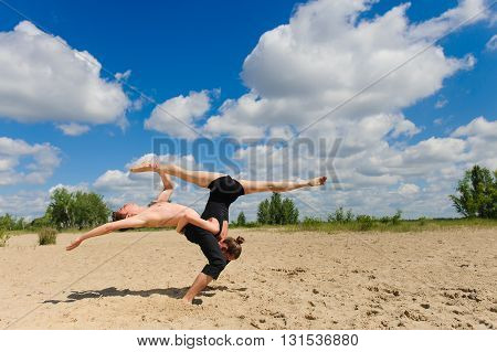 Contemporary dance. Man and woman in passionate dance pose on beach. Young couple dancing modern dance in beautiful pose outdoors. Girl doing splits against the sky clouds. A man with naked torso on sand.