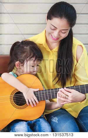 Mother With Daughter Play Guitar. Family Spending Time Together At Home.