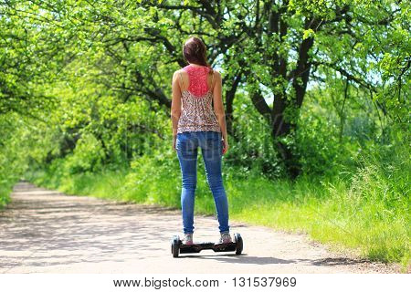 young woman riding electrical scooter outdoor - personal eco transport, hoverboard, gyro scooter, hyroscooter, smart balance wheel