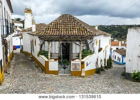 Obidos Portugal - March 20 2016: Obidos Portugal a medieval city encircled by a fortified wall. Its streets squares walls and its massive castle have turned the picturesque village into a preferred tourist attraction in Portugal.