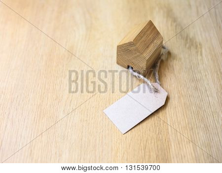 Home Model with Paper gift Tag on wooden background Real estate Concept