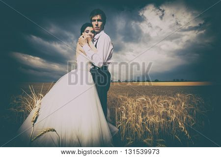 Bride And Groom In Wheat Field With Dramamtic Sky