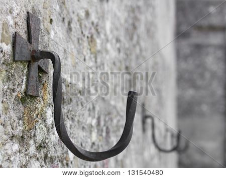 Iron hook on the wall with decoration in the shape of a cross. Defocused blurry background.