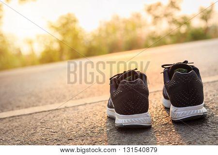 New Black Running Shoes On Asphalt Road In Morning Time