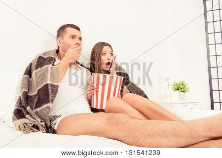 Afraid Man And Woman Watching Horror Film With Popcorn Before Sleep