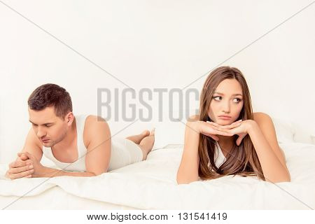 Portrait Of Young Couple Lying In Bed After Quarrel