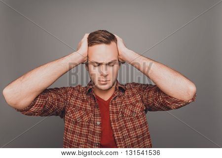 Portrait of young businessman touching head and having big problems