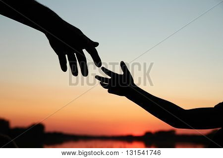 a silhouette of parent holds the hand of a small child