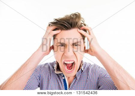 Portrait Of Young Frusrated Angry Man Screaming And Holding Head