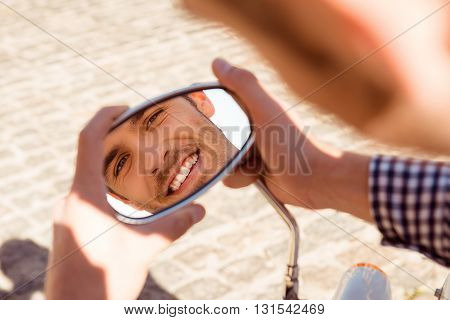 Reflection of a young handsome man in the mirror of bike