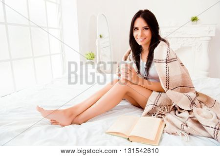 Beautiful Romantic Young Woman With Book Basking With Tea And Blanket In Bedroom