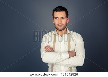 Serious strict man with crossed hands  on a gray background