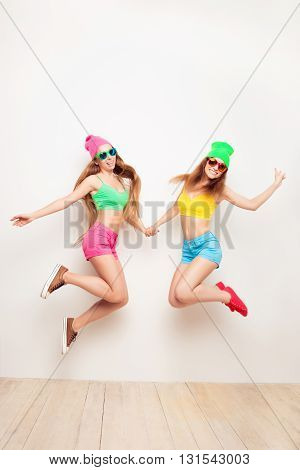 Attractive Hipster Girls In Glasses Feeling Free And Jumping
