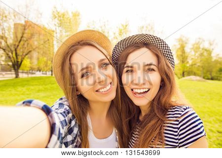 Two Cheerful Smiling Sisters Making Selfie And Showing Tongue