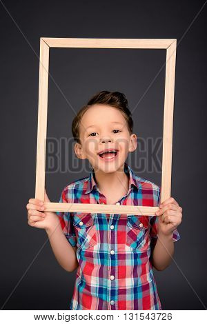 Cheerful Happy Laughing Little Boy Holding Wooden Frame