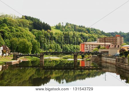sluice on the river Jizera on the background of nature sky and buildings in the foreground river