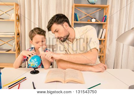 Little Boy And His Father Learning Geography At Home