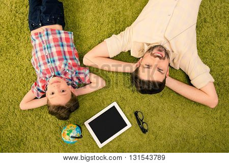Happy Little Boy And His Father Lying On Carpet And Dreaming