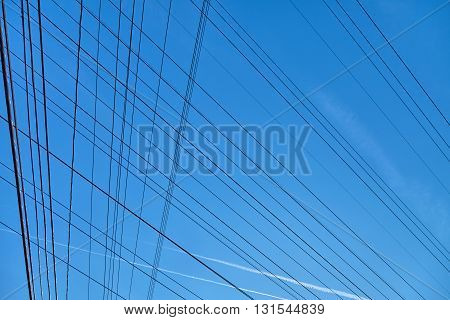 Plurality of electrical wire against the bkue sky.