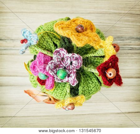 Symbolic knitted bouquet on the wooden background. Gift item. Holiday symbol. Special gift. Lovely object. Artistic symbol.