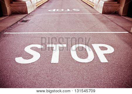 Stop written on red asphalt - concept image