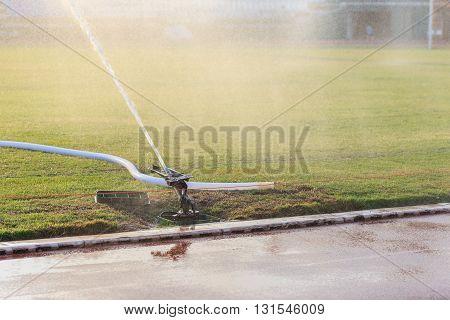 Sprinkler Spraying Water To Grass Field In Football Stadium