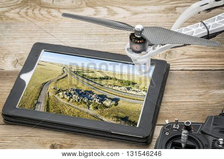 Aerial photography concept - reviewing picture of Natural Fort, highway and prairie on a digital tablet with a drone and radio controller. Screen picture copyright by the photographer.