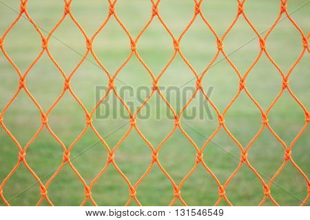 Orange Soccer Net On Green Grass Background