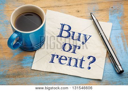Buy or rent question  - handwriting on a napkin with a cup of espresso coffee