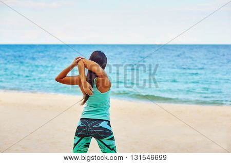 Young woman stretching on the beach , sport activities
