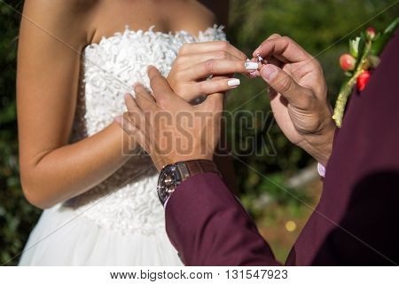 groom wears the ring bride. wedding ceremony outdoors